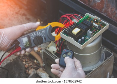 Technician man hand holding and using digital clamp meter to check the functional and test the electrical current  at control panel of motor gear of home auto door remote control.Maintenance  concept.