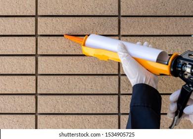 Technician man hand holding and using glue gun, silicone tube or manual caulking gun to fix the sandstone. Maintenance concept.