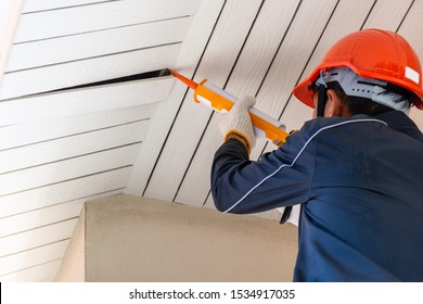 Technician man hand holding and using glue gun, silicone tube or manual caulking gun to repair and fix the wooden cornice with the ceiling at the under roof at home exterior.