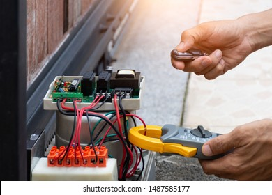 Technician man hand pressing remote control while repair and using digital clamp meter to test and check the functional and  the electrical current at control panel of motor bridge gear of auto garage