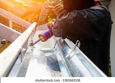 Technician man hand using glue gun with silicone adhesive or manual caulking gun with polyurethane to fix the metal steel. Installing and construction concept.