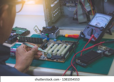 Technician man repairing and changing the battery of motherboard. Selective focus.