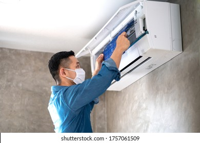 Technician man repairing ,cleaning and maintenance Air conditioner on the wall in bedroom or office room.On site home service,Business ,Industrial concept.