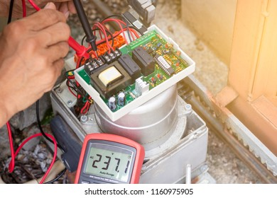 Technician man testing and checking electrical voltage at controlled main board of automatic gate auto gear by mulitmeter, maintenance concept.