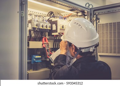 Technician is measuring voltage or current by voltmeter in control panel of power plant, selective focus on safety helmet