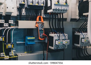 Technician is measuring voltage or current by voltmeter in control panel of power plant