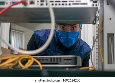 A technician in a medical mask works in a rack with computer equipment. The man serves the server room in the datacenter. Portrait of a teenager in a data center.