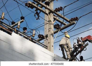 Technician men fixing or repairing broken power line, a dangerous job background
