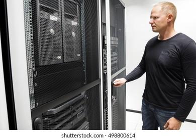 Technician Opening Server Rack Door In Data Center
