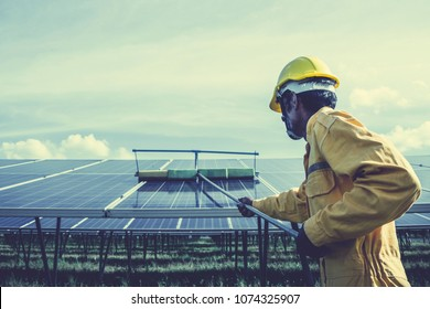 technician operating and cleaning solar panels at generating power of solar power plant; technician in industry uniform on level of job description at industrial