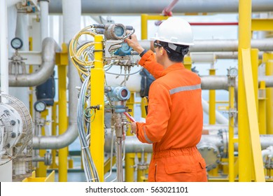Technician operator checking reading value from pressure and temperature transmitter of oil and gas process to find abnormal condition, Offshore business and occupational.