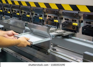 The technician operator handing the sheet metal part with  hydraulic bending machine. Metal working concept