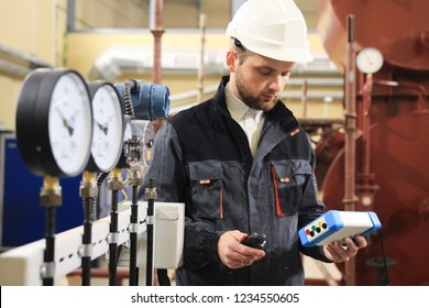 Technician operator measuring value of pressure, temperature and flow on gas and oil processing platform to monitor quality of process