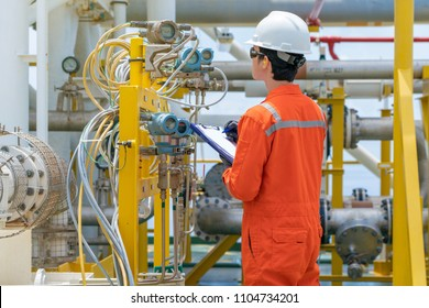 Technician operator record reading value of pressure, temperature and flow at offshore oil and gas central processing platform to monitor quality of process.