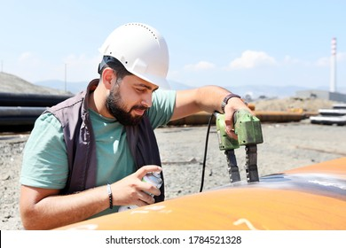"""A technician performs MPI on a pipeline to check for stress corrosion cracking using what is known as the """"black and white"""" method. is a non-destructive testing (NDT) process for detecting surface."""