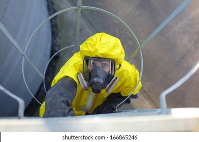technician in protective uniform and mask  going up a metal ladder