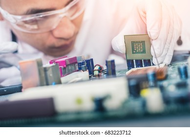 The technician is putting the CPU on the socket of the computer motherboard. the concept of computer hardware, repairing, upgrade and technology.