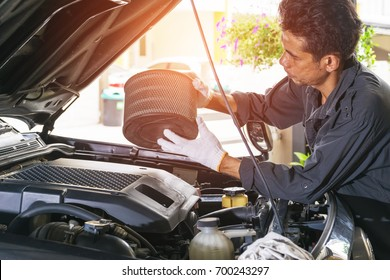 The technician removes the car's air filter for inspection and cleaning, Automotive industry and garage concepts.