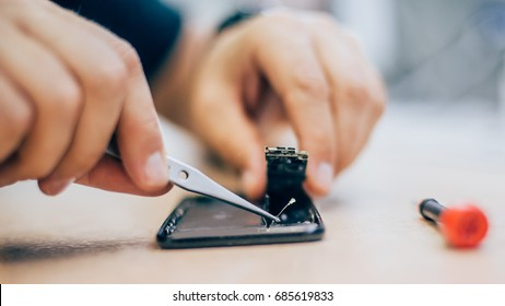 Technician repair faulty mobile phone in electronic smart phone technology service.Cellphone technology device maintenance engineer