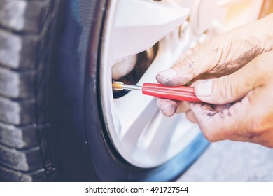 Technician is repairing car flat tire