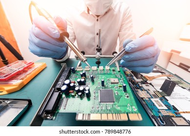The technician repairing the computer mainboard by soldering in the lab. The concept of computer hardware, repairing, upgrade and technology.
