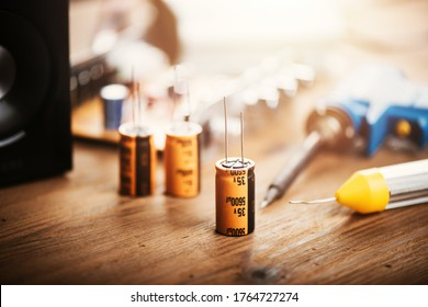 Technician repairing the electronic device. Reparing the audio amplifier. Close up at the orange capacitor.