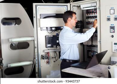 technician repairing industrial machine with laptop computer
