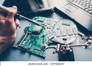 Technician repairing pcb layout with soldering iron. Broken disassembled laptop. Electronic components. Computer analysis.