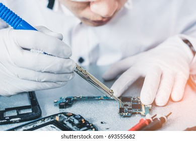 The technician repairing the smartphone's motherboard by soldering in the lab. the concept of computer hardware, mobile phone, electronic, repairing, upgrade and technology.