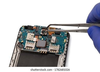 A technician repairs a smartphone camera module. Smartphone repair concept. Camera of the smartphone is taken with tweezers