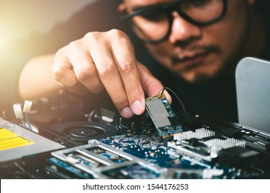 Technician reparing a broken computer. Computer service and repair concept.