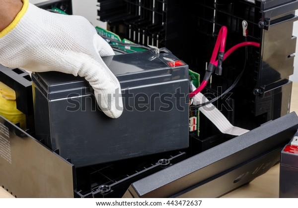 Technician replacing the UPS(Uninterruptible Power Supply) battery.