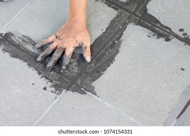 ?hand of technician sample wrong work on gray color of new cement grout on tile gray for the final step for flooring in Thailand.