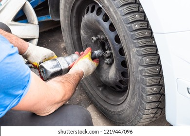 technician screws a winter car wheel by pneumatic torque wrench outdoors during seasonal replacement of tires