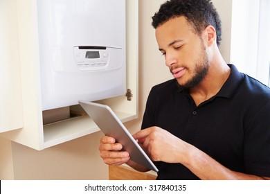 Technician servicing a boiler using tablet computer