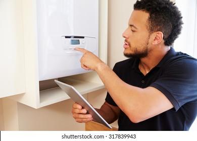 Technician servicing a boilerholding tablet computer