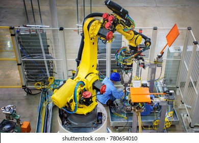 Technician setting new robot for industrial machine welding in production line of vehicle factory