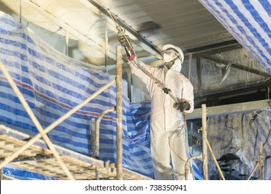 Technician spraying foam insulation using Plural Component Gun for polyurethane foam - Repair tool in the white protect suit applies a construction foam from the gun to the roof of a warehouse.