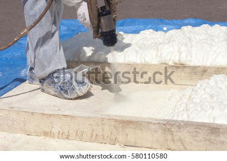 Technician Spraying Foam Insulation Using Plural Stock Photo
