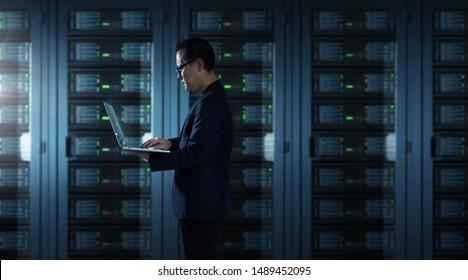 IT Technician in suit works on laptop working in server room .