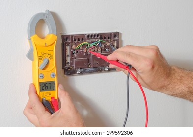 Technician testing thermostat voltage with a voltage meter