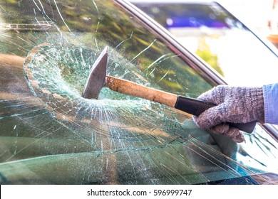 Technician use hammer for Broken car windshield. Selective focus.