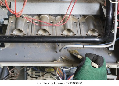 Technician using brush to clean under burners on a gas furnace.