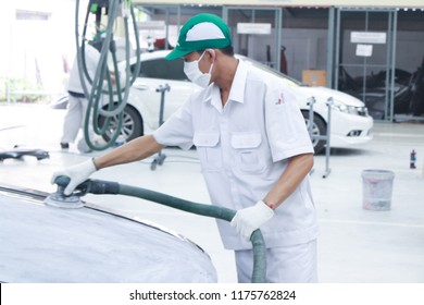 The technician is using a car polishing machine  in auto repair Body and Paint car Shop. car care concept. soft focus photo