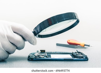 The technician using the magnifying glass for repairing the smartphone's motherboard in the lab. the concept of computer hardware, mobile phone, electronic, repairing and technology.