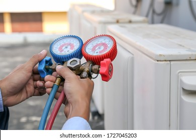 Technician using manifold gauge is measuring equipment for filling industrial factory air conditioners and checking maintenance outdoor air compressor unit.