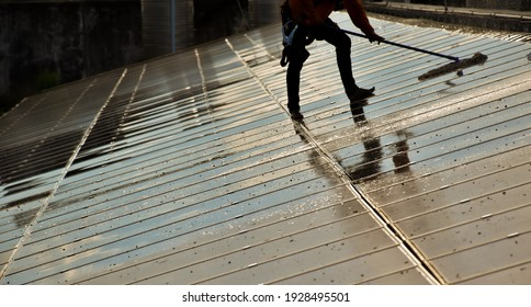 Technician is using a mop and water to clean the solar panels that are dirty with dust and birds' droppings to improve the efficiency of solar energy storage even better. Soft and selective focus.