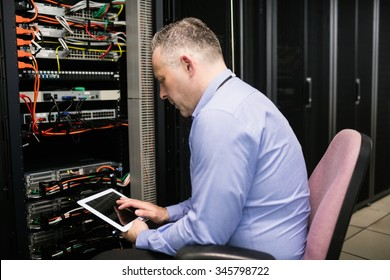 Technician using tablet in server room at the data centre