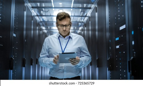 IT Technician Walks Through Rows of Server Racks in Data Center. Simultaneously He Works on a Tablet Computer.
