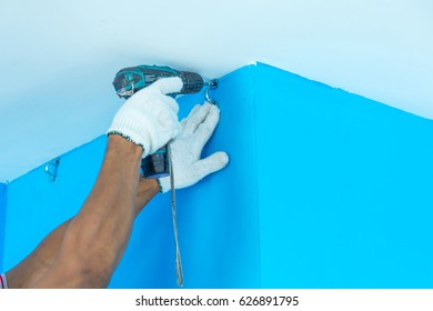 Technician wearing white gloves uses cordless driver drill to screw nail on the blue wall.